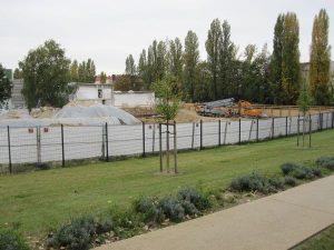 Blick auf abgedeckten belasteten Boden und Baustelle am Park